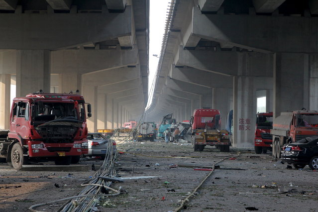 Damaged vehicles are seen under bridges close to the site of the explosions at Binhai new district, Tianjin, August 13, 2015. (Photo by Reuters/Stringer)