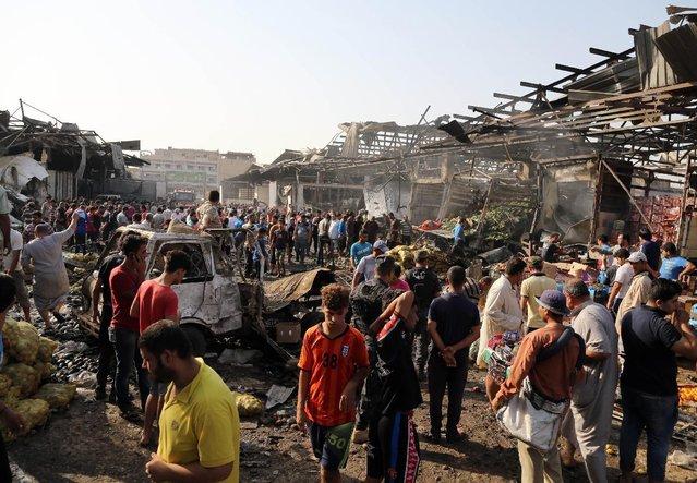 Civilians gather at the scene of bomb attack in Jameela market in the Iraqi capital's crowded Sadr City neighborhood Baghdad, Iraq, Thursday, August 13, 2015. (Photo by Karim Kadim/AP Photo)