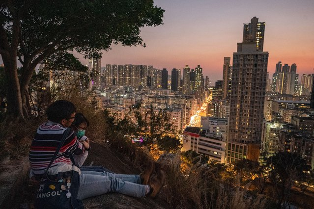 A couple wears face masks as they share a moment during sunset on January 31, 2020 in Hong Kong, China. With over 9800 confirmed cases of Novel coronavirus (2019-nCoV) around the world, the virus has so far claimed over 200 lives. (Photo by Anthony Kwan/Getty Images)