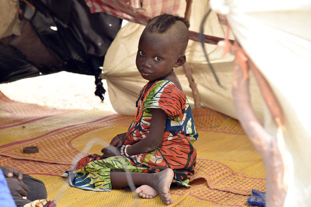 A child looks on under a makeshift tent in a camp in the village of Kidjendi near Diffa on June 19, 2016 as displaced families fled from Boko Haram attacks in Bosso. Earlier this month 24 soldiers from Niger and two Nigerian troops were killed in a Boko Haram attack in the Bosso area of Niger, near Lake Chad, prompting Chad to send in reinforcements. (Photo by Issouf Sanogo/AFP Photo)
