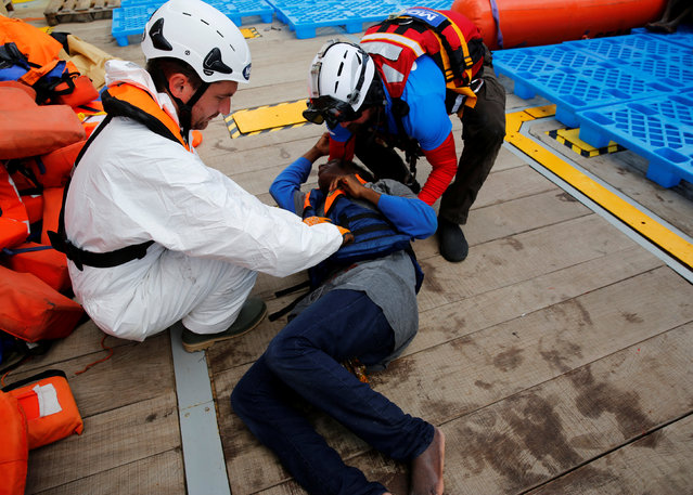 A collapsed migrant is assisted by Migrant Offshore Aid Station (MOAS) rescuers after boarding the MOAS ship Topaz Responder around 20 nautical miles off the coast of Libya, June 23, 2016. (Photo by Darrin Zammit Lupi/Reuters)