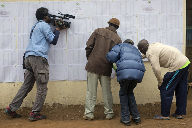 A television cameraman films Kenyans checking if their names are on the electoral lists at a polling station in the Kibera slum in Nairobi, Kenya, Monday August 7, 2017. (Photo by Jerome Delay/AP Photo)