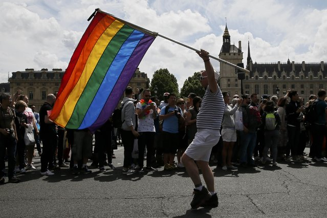 A participant waves a rainbow flag during the annual LGBT Paris Pride parade in Paris, France, July 2, 2016. (Photo by Gonzalo Fuentes/Reuters)