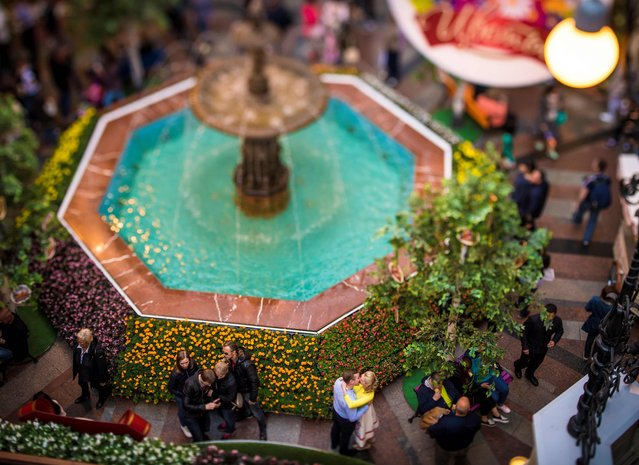 A picture taken with a tilt and shift lens shows near a fountain in the high-end GUM (State Department Store) shopping centre in Moscow on July 9, 2017. (Photo by Mladen Antonov/AFP Photo)