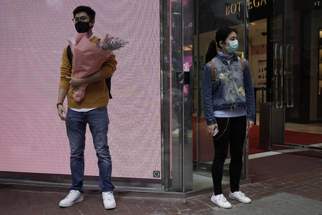 A man wearing protective face mask waits at a street corner with a bouquet on Valentine's Day in Hong Kong, Friday, February 14, 2020. (Photo by Kin Cheung/AP Photo)