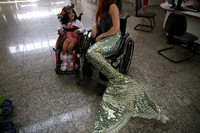 "Mermaid Carol Catan visits the Disabled Child Care Association (AACD) in Sao Paulo, Brazil June 8, 2017. Children with disabilities being treated at Brazil's hospitals, where economic hardship has crimped services, are getting an emotional lift from a mythical creature of the sea: a mermaid. But in this instance, the siren is quite real. Carol Catan has earned her living portraying a mermaid and teaching mermaiding since 2012, when she left her job of 10 years as a veterinarian. She is paid for performing at events such as children's parties but donates her time at hospitals. Dressed in costume with a long, shiny green tail, she chats with young patients and ""they feel included, cherished. It is a very beautiful and gratifying thing"". (Photo by Pilar Olivares/Reuters)"