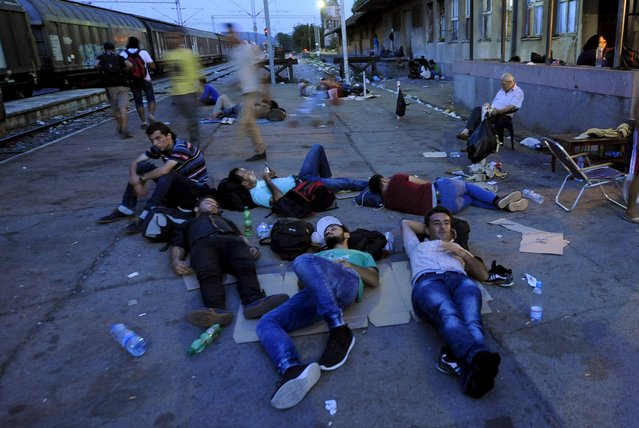 Immigrants rest on a platform at Gevgelija railway station, Macedonia August 19, 2015. (Photo by Ognen Teofilovski/Reuters)