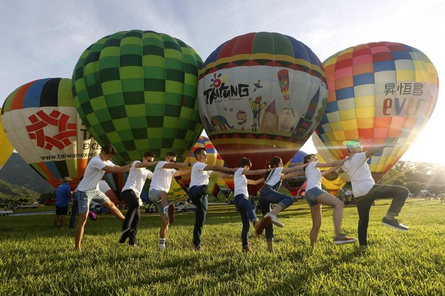 Visitors play in front of hot air balloons during the 2016 International Hot Air Balloon Festival in Taitung, southeast of Taiwan, 01 July 2016. (Photo by Ritchie B. Tongo/EPA)
