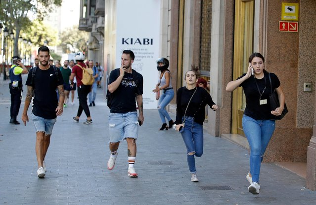 People run down a street in Barcelona, Spain, Thursday, August 17, 2017. Police in the northern Spanish city of Barcelona say a white van has jumped the sidewalk in the city's historic Las Ramblas district, injuring several people. (Photo by Manu Fernandez/AP Photo)