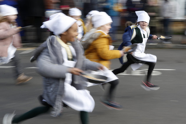 Schoolchildren from local schools take part in the children's races prior to the annual Pancake race in Olney, Buckinghamshire, England, Tuesday, February 25, 2020. Every year women clad in aprons and head scarves from Olney and the city of Liberal, in Kansas, USA, run their respective legs of the race with pancakes in their pans. According to legend, the Olney race started in 1445 when a harried housewife arrived at church on Shrove Tuesday still clutching her frying pan with a pancake in it. (Photo by Alastair Grant/AP Photo)