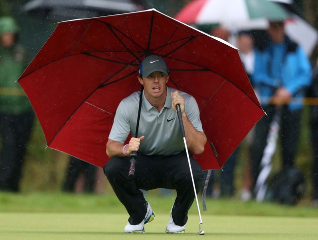 Rory McIlroy kneels under an umbrella as he waits to play on the 4th green during the third day of the British Open at the Royal Liverpool golf club in Hoylake, England, on Jule 19, 2014. McIlroy  finished the round with a six stroke lead. (Photo by Jon Super/Associated Press)
