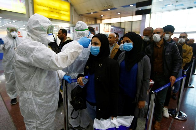Iraqi medical staff check passengers' temperature, amid the new coronavirus outbreak, upon their arrival at Najaf airport, Iraq on February 20, 2020. (Photo by Alaa al-Marjani/Reuters)
