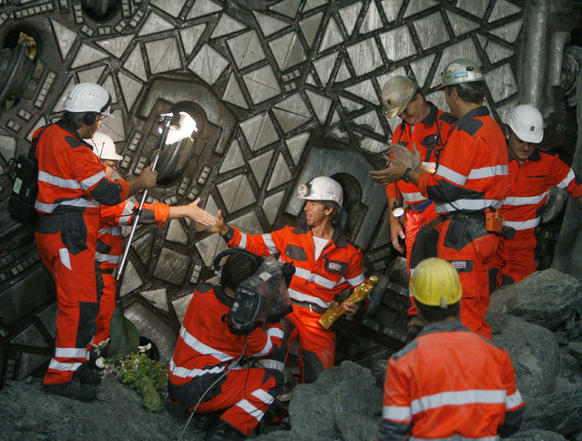 A miner holds a statue of St. Barbara, patron saint of miners, as he is welcomed by colleagues after the drill machine 'Gaby' made it through the section Erstfeld-Amsteg at the construction site of the NEAT Gotthard Base Tunnel June 16, 2009. (Photo by Arnd Wiegmann/Reuters)