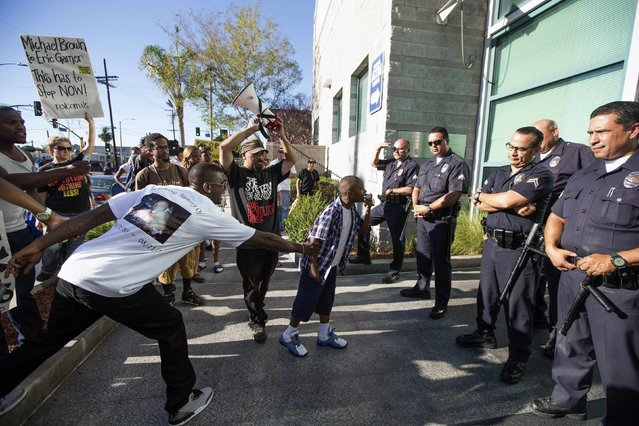 People protest the fatal police shooting of Ezell Ford, who died during an August 11, 2014 confrontation with police in South Los Angeles, at a rally outside the Newton area police station in Los Angeles, California August 15, 2014. (Photo by Lucy Nicholson/Reuters)
