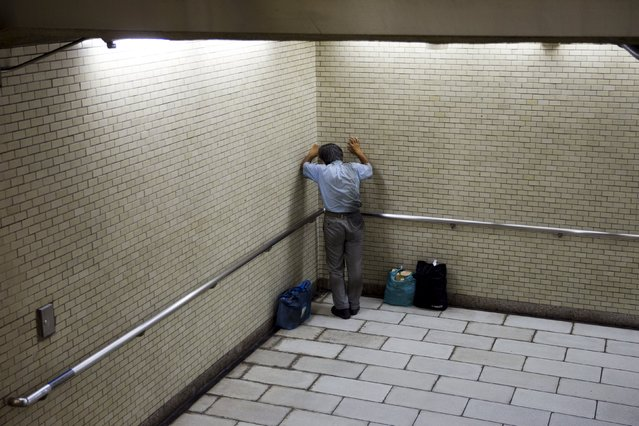 A man in soiled business clothes leans in the corner of a subway underpass in Tokyo, July 26, 2015. (Photo by Thomas Peter/Reuters)