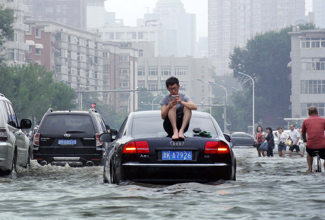 A man sits on top of a car as he is stranded on a flooded street in Tianjin, China, July 20, 2016. (Photo by Reuters/Stringer)