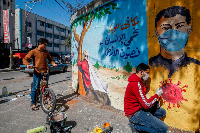 """A Palestinian artist paints a mural reading """"By fighting the epidemic, we protect the human being and preserve the earth"""" as a youth watches him in Rafah in the southern Gaza Strip, on March 29, 2020. (Photo by Mohammed Abed/AFP Photo)"""