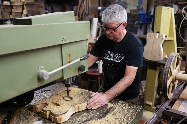 Rick Kelly, owner of Carmine Street Guitars, works on a guitar made from discarded yellow and white pine wood at his shop in New York City, U.S., July 21, 2016. (Photo by Joe Penney/Reuters)