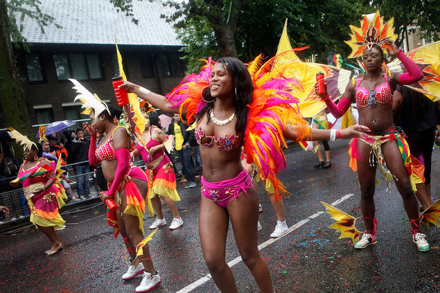 Performers dance through heavy rain during the Notting Hill Carnival on August 25th, 2014 in London, England.   (Photo by Mary Turner/Getty Images)