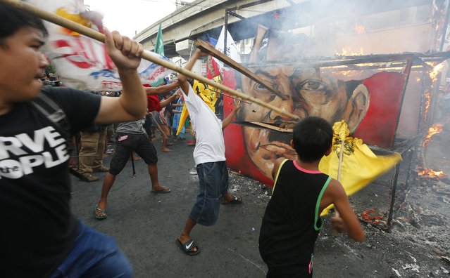 """Protesters hit the burning cube effigy with the faces of the late dictator Ferdinand Marcos and President Rodrigo Duterte during a rally near the Presidential Palace to call for an end to the killings in the so-called war on drugs of Duterte and his alleged """"tyrannical rule"""" in the country Thursday, September 21, 2017 in Manila, Philippines. Thousands of protesters are marking the anniversary of the 1972 martial law declaration by late Philippine dictator Ferdinand Marcos with an outcry against what they say is the current president's authoritarian tendencies and his brutal crackdown on illegal drugs. (Photo by Bullit Marquez/AP Photo)"""