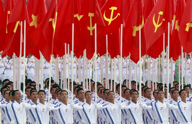 Men carry communist and Vietnamese national flags during a parade marking their 70th National Day at Ba Dinh square in Hanoi, Vietnam, September 2, 2015. (Photo by Reuters/Kham)