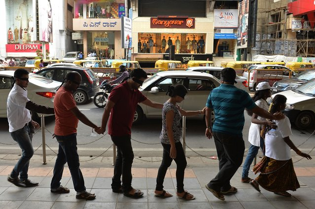 "Indian participants wearing blindfolds follow visually-impaired volunteers as they take part in a ""Blind Walk"" in Bangalore on August 24, 2014. Over 600 residents participated in the ""Project Vision"" event which aimed to raise awareness for the visually-impaired. (Photo by Manjunath Kiran/AFP Photo)"