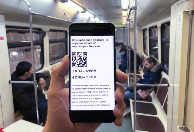 In this photo taken on late Tuesday, April 14, 2020, a man shows the electronic passes with a QR-code displayed on smartphone screen as he rides Moscow Metro (subway) in Moscow, Russia. All Moscow residents who use public or private phones are required to obtain electronic passes starting Wednesday. Russian President Vladimir Putin has ordered most Russians to stay off work until the end of April as part of a partial economic shutdown to prevent the spread of the coronavirus. (Photo by Moscow News Agency Photo via AP Photo)