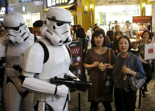 """Workers dressed as Storm Troopers from """"Star Wars"""" march on a street as tourists watch at Myeongdong shopping district in Seoul, South Korea, September 4, 2015. (Photo by Kim Hong-Ji/Reuters)"""