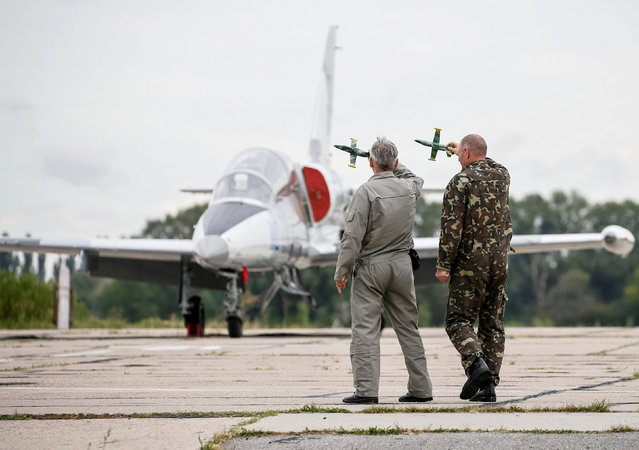 Pilots plan a flight manoeuvre with model aircraft at a military air base in Vasylkiv, Ukraine, August 3, 2016. (Photo by Gleb Garanich/Reuters)