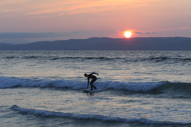 A young surfer catches a wave on a deserted Castlerock beach, County Londonderry, Northern Ireland as the sun sets over Donegal, Ireland on April 25, 2020 in Castlerock, Northern Ireland. The British government has extended the lockdown restrictions first introduced on March 23 that are meant to slow the spread of COVID-19. (Photo by Michael Cooper/Getty Images)