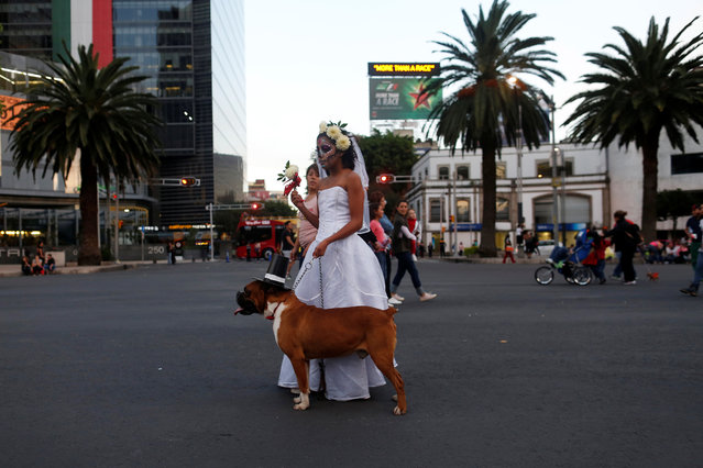 """A woman dressed up as """"Catrina"""", a Mexican character also known as """"The Elegant Death"""", stands with her dog during a Catrinas parade in Mexico City, Mexico on October 22, 2017. (Photo by Carlos Jasso/Reuters)"""