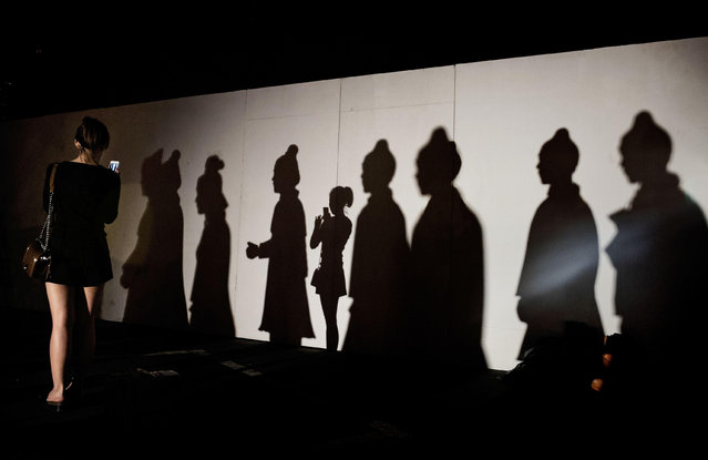 A Chinese woman takes a picture of herself as she casts a shadow next to the shadows of statues replicating China's famous Terracotta Warriors at an exhibtion on September 3, 2014 in Beijing, China. (Photo by Kevin Frayer/Getty Images)