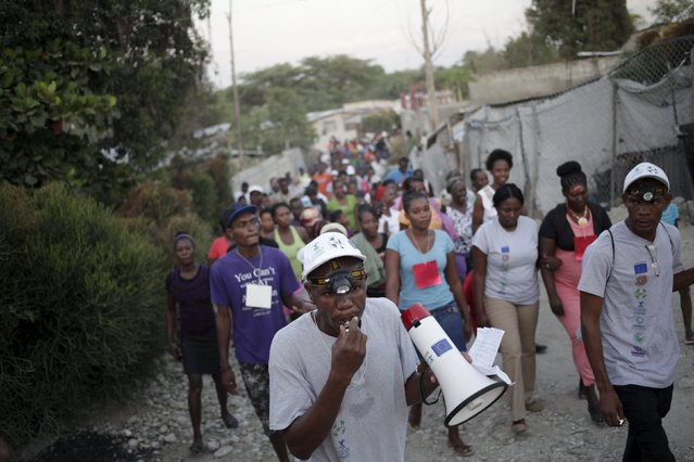 A member of the Emergency and Intervention Units calls local residents to join them during an emergency evacuation drill in Tabarre, on the outskirts of Port-au-Prince, Haiti, February 25, 2016. (Photo by Andres Martinez Casares/Reuters)
