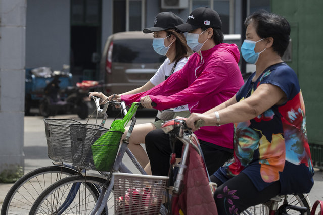 Residents wearing masks to curb the spread of the coronavirus ride past a neighborhood under lockdown in Beijing Tuesday, June 16, 2020. Chinese authorities locked down a third neighborhood in Beijing on Tuesday as they rushed to prevent the spread of a new coronavirus outbreak that has infected more than 100 people in a country that appeared to have largely contained the virus. (Photo by Ng Han Guan/AP Photo)