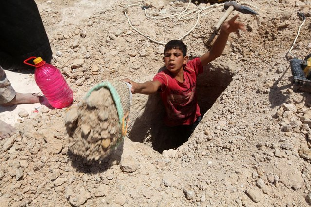 """A boy digs a grave at the Wadi al-Salam cemetery, Arabic for """"Peace Valley"""", in Najaf, south of Baghdad, Iraq July 27, 2016. (Photo by Alaa Al-Marjani/Reuters)"""