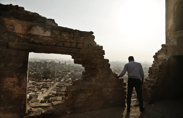 A man looks at the general view of a cemetery from the Shahin Al-Khalwati Mosque in Cairo, Egypt, Wednesday, August 24, 2016. Muslim Sufi Saint Shahin Al-Khalwati built the mosque in the 16th century on top of a hill where he would go into spiritual seclusion. Today the neglected mosque sits on the top of a hill of a cemetery. Al-Khalwati's grandchildren demand the government restore the mosque because it is a heritage site according to civilians who live in the cemetery area. (Photo by Nariman El-Mofty/AP Photo)