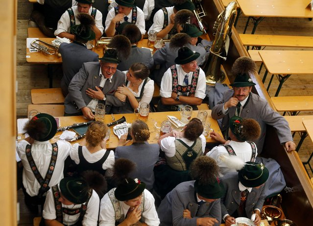 People dressed in traditional Bavarian clothes sit inside a beer tent after the Oktoberfest parade in Munich, Germany, September 20, 2015. (Photo by Michael Dalder/Reuters)