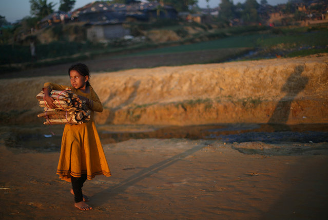 A Rohingya refugee girl carries wood through the Kutupalong refugee camp at sunset near Cox's Bazar, Bangladesh, November 4, 2017. (Photo by Hannah McKay/Reuters)