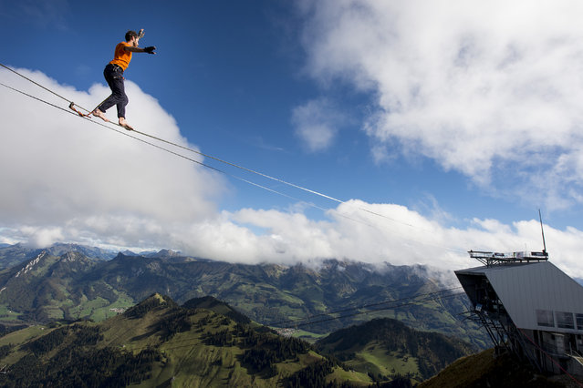 "Guillaume Roland, a professional mountaineer, balances on the ""highline"" during the European Highline Meeting on the top of the Moleson mountain at 2,000 meters above the sea level, in the Swiss Alps, near Fribourg, Switzerland, October 17, 2014. (Photo by Jean-Christophe Bott/EPA)"