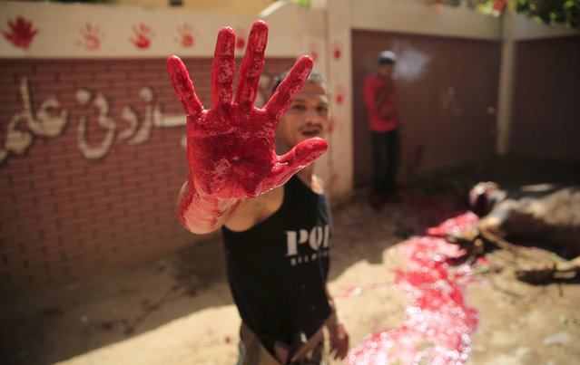 A butcher shows his bloodied handfrom a just-slaughtered calf on the first day of Eid al-Adha festival in Toukh, El-Kalubia governorate, northeast of Cairo, Egypt, September 24, 2015. (Photo by Amr Abdallah Dalsh/Reuters)