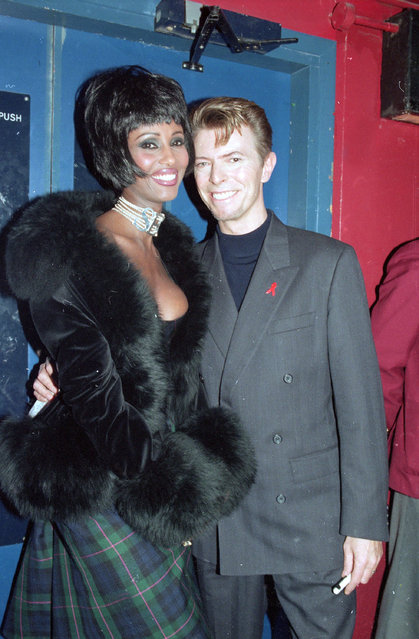 """British rock singer David Bowie and his wife, supermodel Iman, are seen backstage at the Prince of Wales """"Concert of Hope"""" to mark World AIDS Day at London's Wembley Arena, on December 1, 1993.  (Photo by Gill Allen/AP Photo)"""