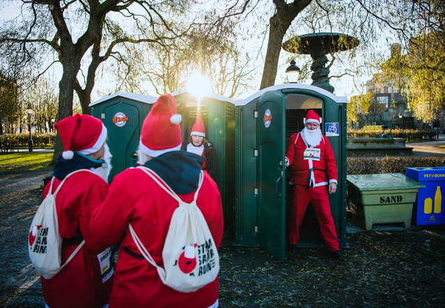 "A charity runner dressed as Father Christmas steps out of a portable toilet ahead of the ""Santa Run"" charity fun run in Stockholm on December 10, 2017. Hundreds of participants dressed in Santa suits and wearing white beards ran through the streets of the old town in Stockholm in an all charity run. (Photo by Jonathan Nackstrand/AFP Photo)"