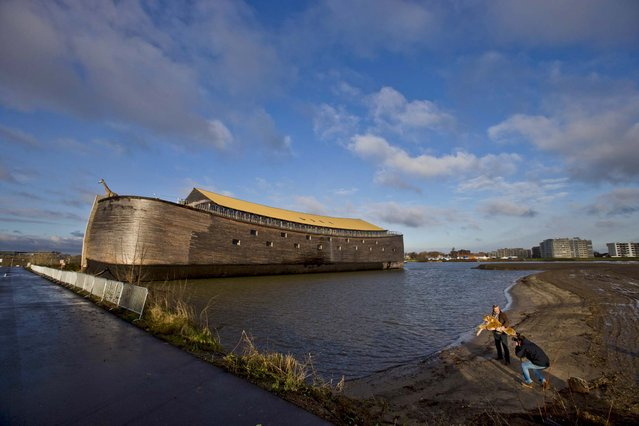 Johan Huibers holds a toy tiger for a photographer in front of the full scale replica of Noah's Ark in Dordrecht, Netherlands, December 10, 2012. Three thousand people a day can visit the replica. (Photo by Peter Dejong/Associated Press)