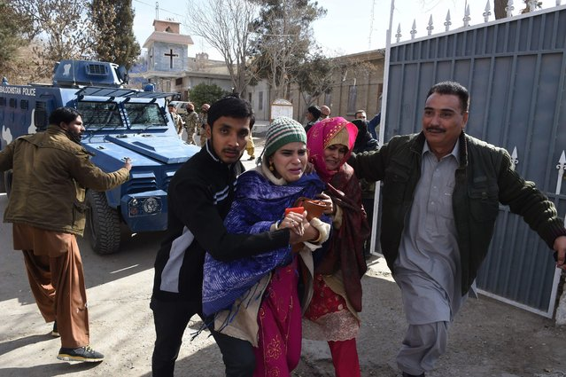 Pakistani Christians are evacuated by security personnel from a Methodist church after a suicide bomber attack during a Sunday service in Quetta on December 17, 2017. At least five people were killed and 15 wounded when two suicide bombers attacked a church in Pakistan during a service on December 17, just over a week before Christmas, police said. The attack took place at the Methodist Church in the restive southwestern city of Quetta in Balochistan province. (Photo by Banaras Khan/AFP Photo)