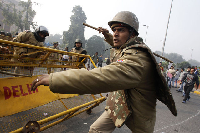An Indian policeman charges with his baton to disperse protesters demonstrating against a gang rape and brutal beating of a 23-year-old student on a bus, in New Delhi, on December 23, 2012. (Photo by Tsering Topgyal/AP Photo)
