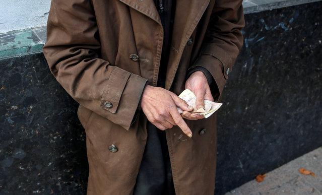 A man counts his money in central Kiev, Ukraine August 31, 2016. (Photo by Gleb Garanich/Reuters)