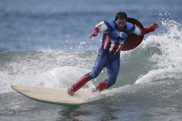 A competitor dressed as Captain America rides a wave during the 7th annual ZJ Boarding House Haunted Heats Halloween surf contest. (Photo by Lucy Nicholson/Reuters)