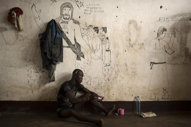 A man sits next to a wall with Christian graffiti in a cell of the central prison in the district of Wango, in Bangui, Central African Republic March 21, 2014. (Photo by Siegfried Modola/Reuters)