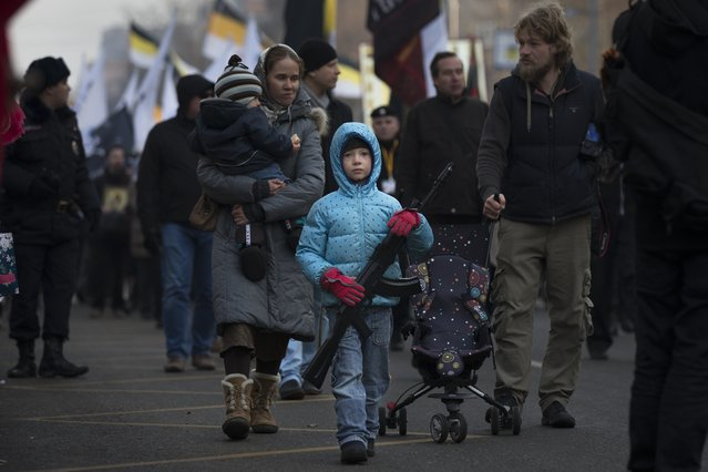 A boy holds a toy rifle during a Russian nationalist march in support of pro-Russian separatists fighting with Ukrainian government forces in eastern Ukraine in Moscow to mark People's Unity Day, a public holiday in Russia, on Tuesday November 4, 2014. (Photo by Alexander Zemlianichenko/AP Photo)