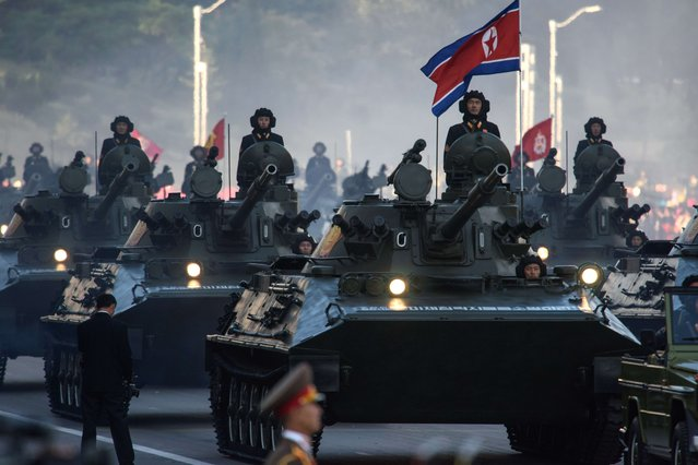 North Korean soldiers ride atop armoured vehicles during a mass military parade at Kim Il-Sung square in Pyongyang on October 10, 2015. (Photo by Ed Jones/AFP Photo)